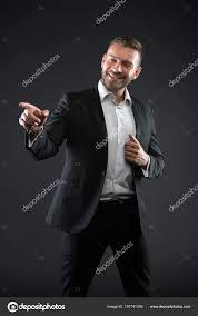 幸せな男は暗い背景に指をポイントします髭の男はフォーマルな