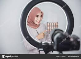 beauty ger makeup tutorial video concept portrait of asian muslim woman showing makeup tutorial using camera and lighting equipment