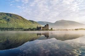 scottish castle in the highlands and its reflection on a lake