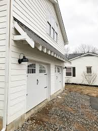 we also bought some galvanized metal barn lights from lowe s and painted them black for each side of the garage doors