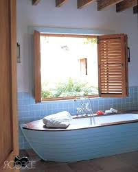blue beach themed bathroom paint colors with freestanding bathtub and single sink vanity under framed mirror