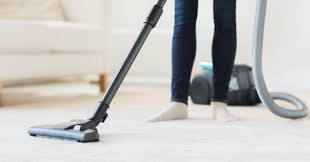 woman vacuum cleaning a carpet