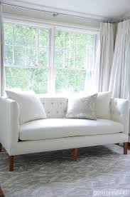 white and grey bedroom with white tufted sofa