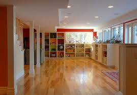 laminate wooden basement flooring ideas with fl fur rug and three white concrete pillars also large shelves plus ceiling lamps