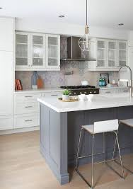 stainless steel vent hood. Seeded Glass Front Kitchen Cabinets Flank A Stainless Steel Vent Hood Mounted To Gray And Blue Mosaic Backsplash Tiles Above Polished Nickel Swing Arm Pot E