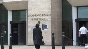 london england circa 2016 woman walks into richmond house home of the