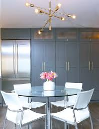 white and gray eat in kitchen with brass modular chandelier