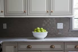 white raised panel kitchen cabinets with gray geometric tile backsplash