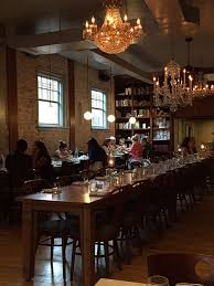 the front dining room at asterisk supper club features crystal chandeliers a long narrow table