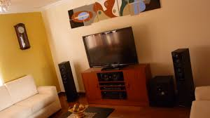 orange wall home theatre room setup white off sofas combined orange wall home theatre room setup white off sofas combined wooden cabinet applied on the wooden floor it also has warm lamp inside living