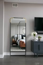 a master bedroom with a black and gold full length mirror