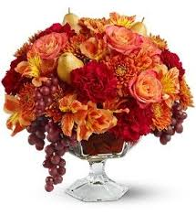 Oh how beautiufl this floral arrangement is in a glass pedestal vase all in  the fall colors of red, burgundy, orange and yellow. We call it Sangria!