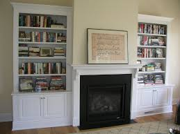 fabulous white wooden built in bookcase cabinet between black painted fireplace added wooden floating shelves as mantel in midcentury living room designs