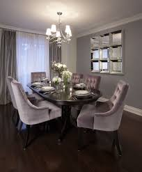 dining room with wall mirror chandelier dark wood table and purple tufted dining chairs lux design