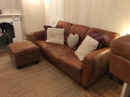 grand saddle leather sofas and foot stools with dark wood feet excellent condition