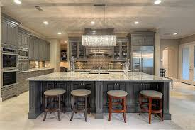 custom wood island in luxury home with metal color cabinets and chandelier