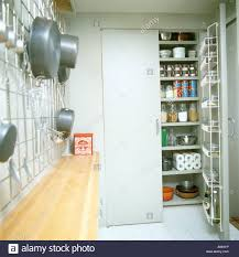 open door to larder cupboard with shelves in galley kitchen with saucepans on metal rack