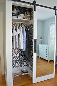 hanging clothes in small closet with wall paper and mirrored barn door