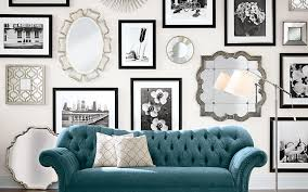 silver mirrors and black and white wall art displayed over a blue sofa