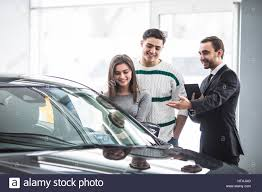 Salon Manager Beautiful Couple Choosing A Car At The Dealership Talking To The