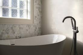 beautiful bathroom boasts a modern freestanding tub and a floor mount gooseneck tub filler alongside a marble hex tiled accent wall