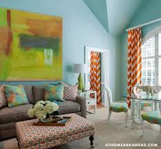 Tobi Fairley - Living room with vaulted ceiling over orange and green  abstract art above modern
