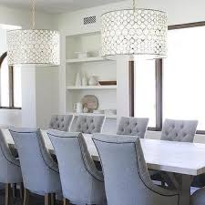 light wood trestle dining table with gray tufted chairs