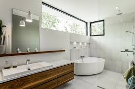 the bathroom features a modish sink area and bathtub along with shower room photo credit