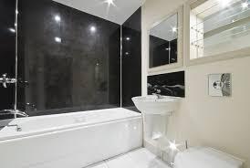 sleek and simple modern bath design uses large black granite tiles on the bathtub