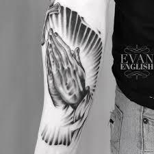 руки молящегося на свету тату на предплечье у парня добавлено