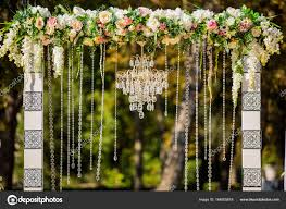 arch for the wedding ceremony decorated with crystal chandelier and fresh flowers wedding decorations the newlyweds photo by wedmov