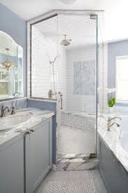 bathroom features gray shaker vanity: exquisite bathroom features a corner shower tiled in beveled subway tile accented with a marble diamond