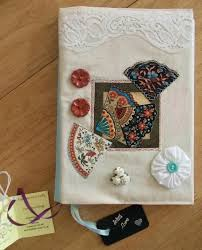 book cover decoration covered in calico and decorated with applique fans finished with ribbon ons paper