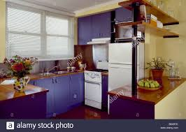 Yellow And Blue Kitchen Slatted Blind On Window On Yellow Kitchen With Blue Units And