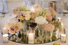 a nicely arranged bouquet of fresh flowers of any color that matches your theme in the center surrounded by various candles in candle glasses surely gives