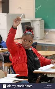 african american girl in th grade english class raises hand while african american girl in 9th grade english class raises hand while writing a personal essay at dunbar high school
