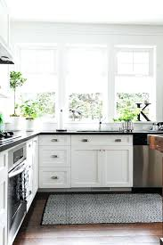 black and white kitchen features shaker cabinets accented with cup pulls topped subway tiled cabinet pull