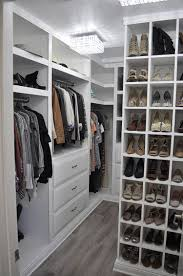very well organized walk-in closet with white cabinets and storage units