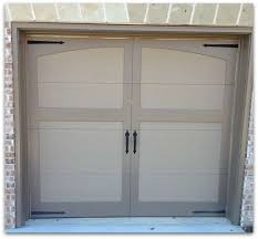 brick home with carriage style garage doors