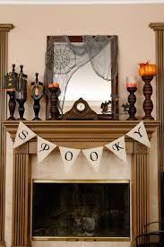 View in gallery Fireplace mantel with spooky candlesticks and banner