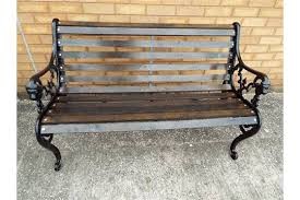 a cast iron garden bench with lion head and wooden slats 77cm x 126cm x 66cm