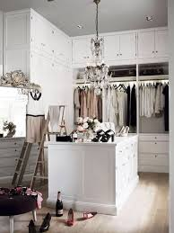 chic walk in closet features small crystal chandelier over closet island surrounded by floor to ceiling built in cabinets accented with ladders and round