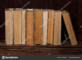 old books stand in row on wooden table stock photo