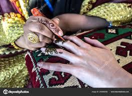 процесс применения хна татуировки красивой стороны молодой девушки