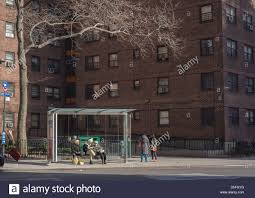 Travelers Wait At A Bus Stop Outside The NYCHA Elliot Houses - New york apartments outside