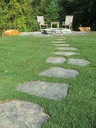 A simple Iron Mountain flagstone path meanders through a lawn to a fire pit  area.