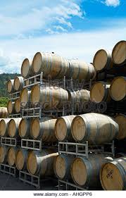 stacked oak wine barrels. A Stack Of Oak Wine Barrels Outside Winery On Sunny Day - Stock Image Stacked