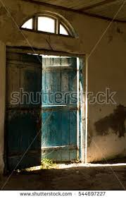 old blue door is ajar and through the pouring sunlight