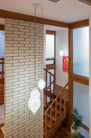a double height brick wall near the stairs adds midcentury charm