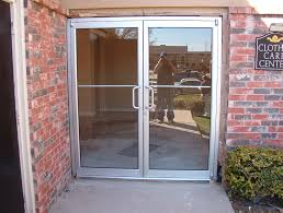 double glass front doors with silver stainless frames and stainless handles connected by brown
